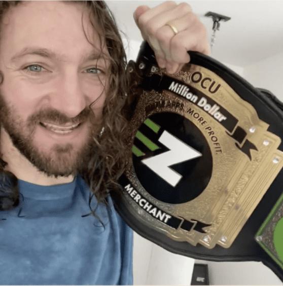 Ezra Firestone holding the OneClickUpsell Million Dollar Merchant belt.